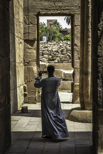 Rear view of man photographing ruined temple
