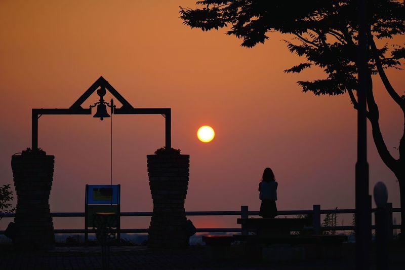 Silhouette people standing by tree against orange sky