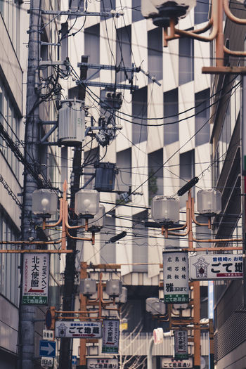 Low angle view of lighting equipment and cables against building