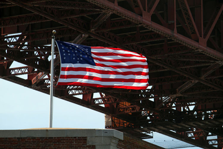 Low angle view of flags against bridge in city