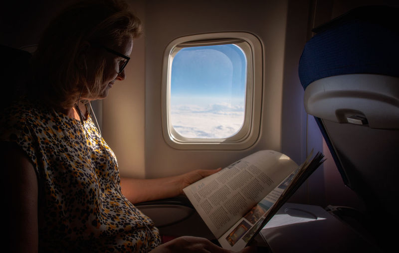 Woman reading magazine on a airplain Passenger Air Vehicle Airplane Casual Clothing Flying Journey Leisure Activity Mode Of Transportation One Person Reading Real People Seat Transportation Travel Vehicle Interior Window Women Flight Passenger Cabin Commercial Airplane The Traveler - 2018 EyeEm Awards The Portraitist - 2018 EyeEm Awards
