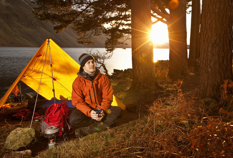 Man sitting at tent against sky during sunset