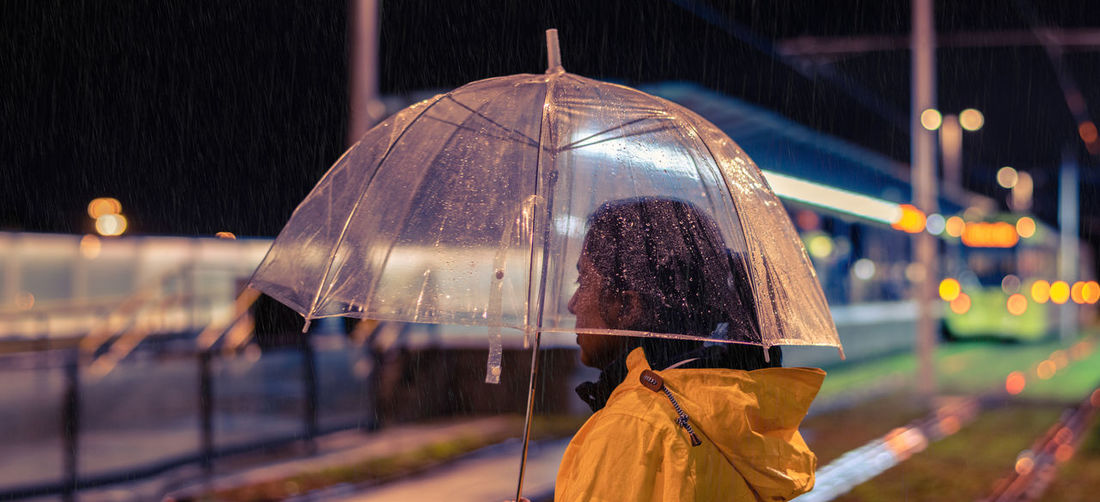 Side View Of Woman Standing With Umbrella In City At Night