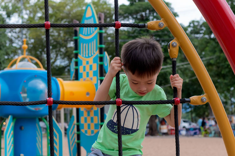 Boy climbing on rope ladder at playground