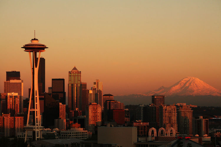 Space Needle Tower In City By Mountain Against Clear Sky During Sunset
