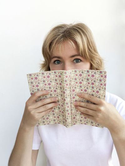 Close-up portrait of woman holding book against white background