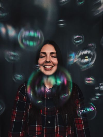 Real People Smiling One Person Happiness Bubble Wand Front View Bubble Cheerful Leisure Activity Beautiful Woman Young Adult Lifestyles Young Women Indoors  Fragility Close-up Day People