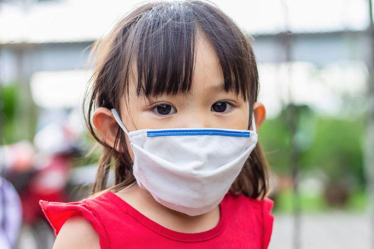 Portrait of cute girl wearing mask outdoors