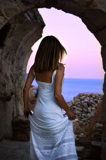 Rear view of woman standing in cave by sea at sunset