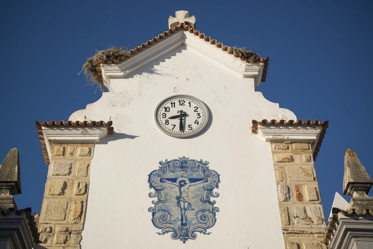 Low Angle View Of Crucifix Painting By Church Against Clear Blue Sky