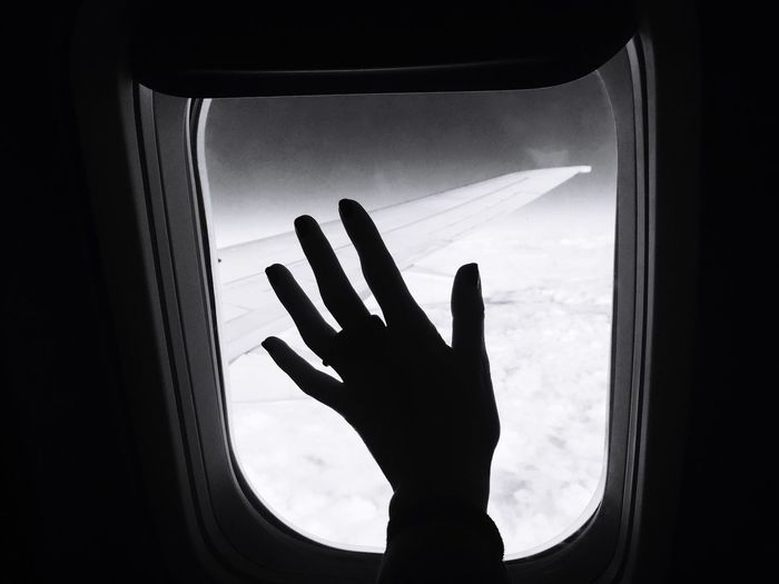 Silhouette Hand Of Woman Touching Airplane Window