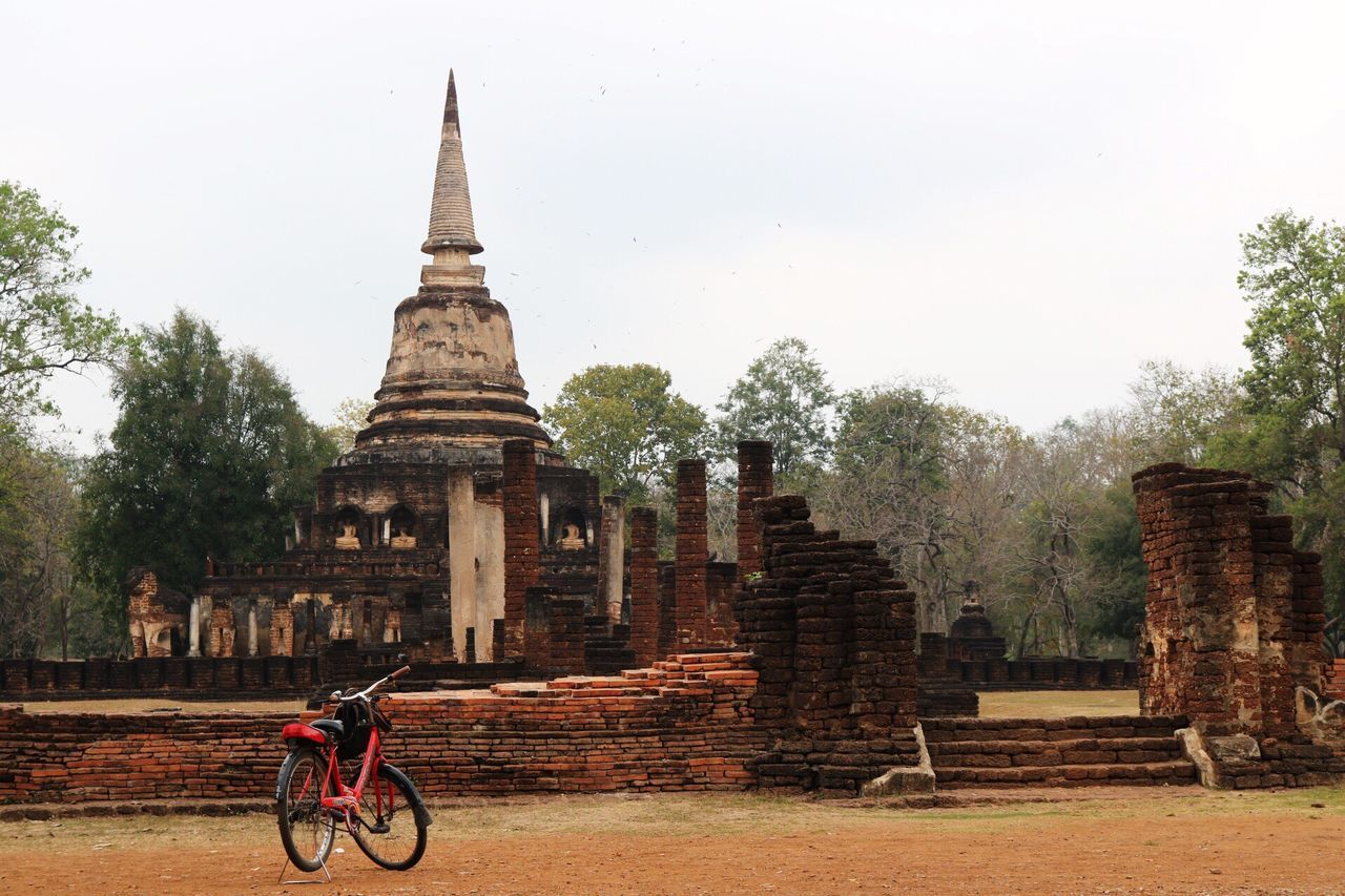 architecture, bicycle, building exterior, built structure, tree, travel destinations, spirituality, cycling, history, place of worship, old ruin, day, men, outdoors, one person, ancient civilization, sky, people
