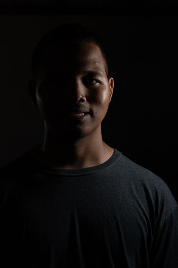 Close-up portrait of young man against black background
