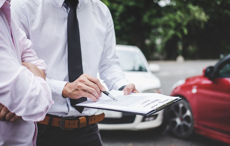 Midsection of agent showing document to man outdoors