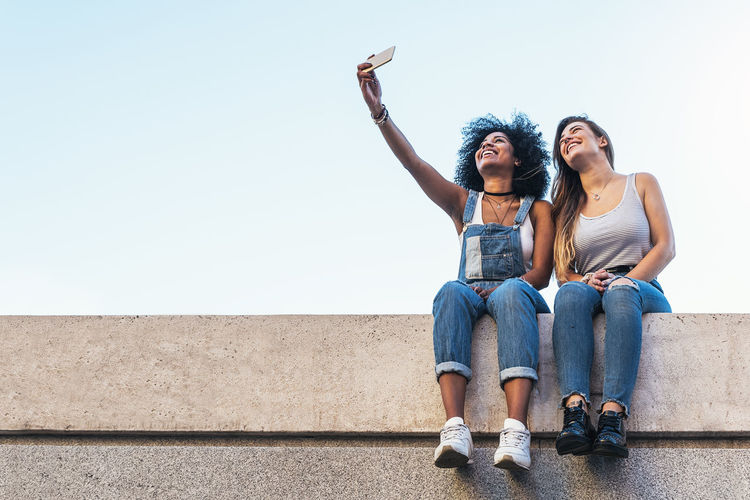 Low angle view of female friends taking selfie while sitting on retaining wall