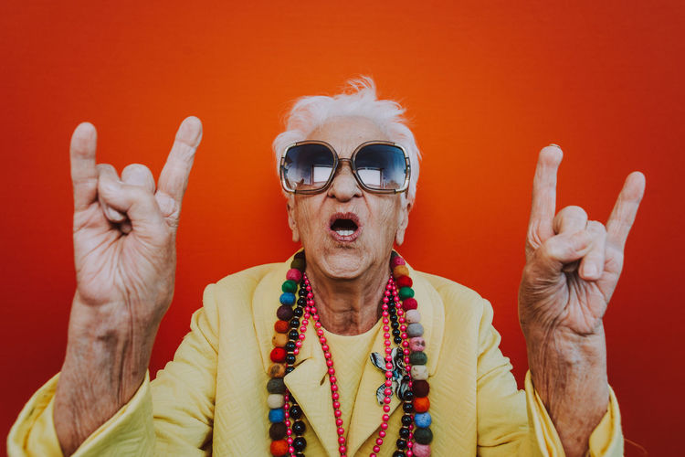 Portrait of senior woman wearing colorful jewelry and sunglasses against red background