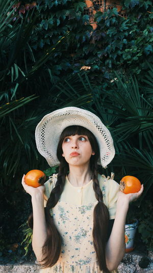 Portrait of young woman wearing hat standing against plants