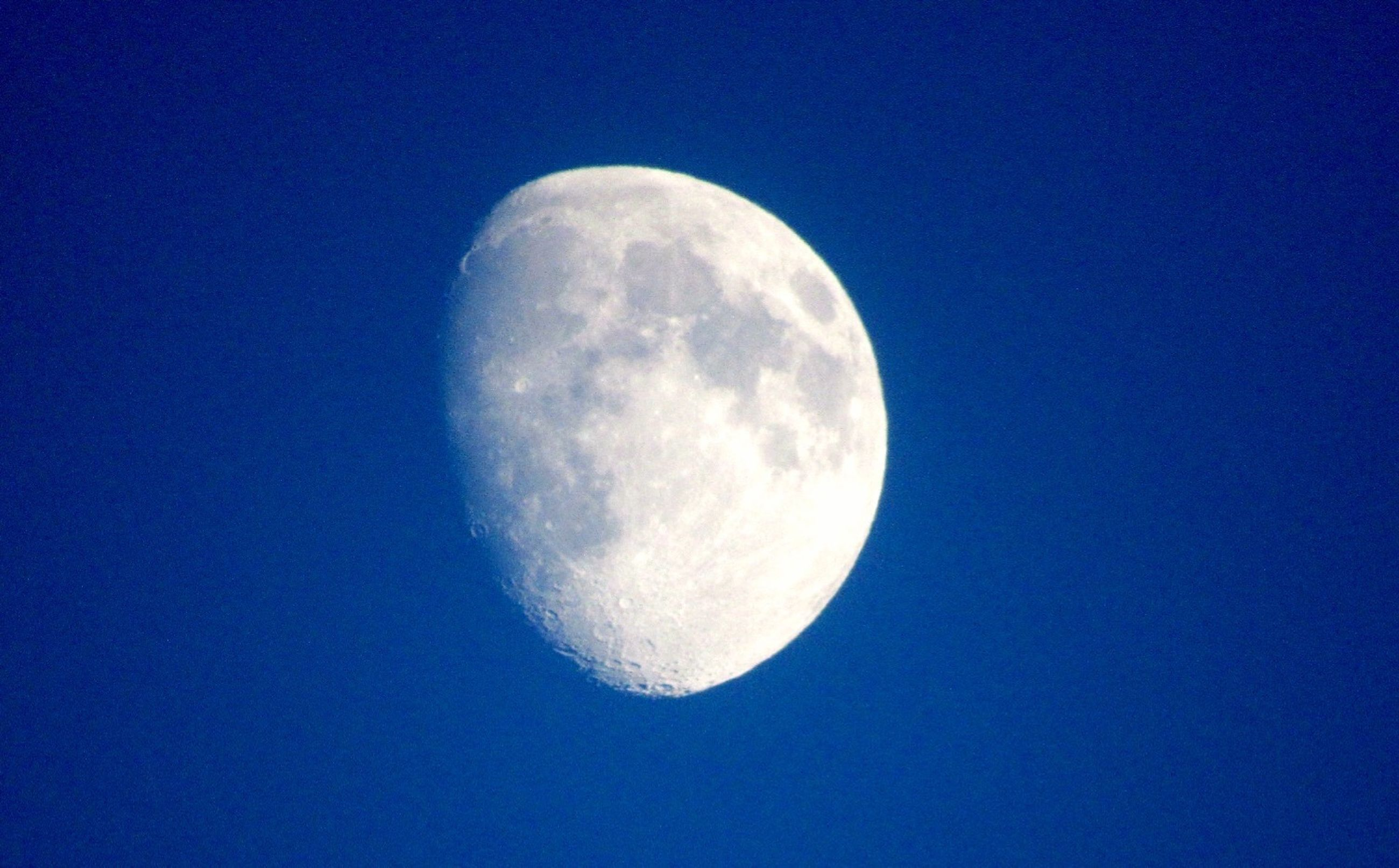 moon, blue, beauty in nature, scenics, clear sky, astronomy, low angle view, tranquil scene, night, tranquility, nature, planetary moon, majestic, moon surface, idyllic, close-up, full moon, sky, space exploration, outdoors, sky only, exploration, space, no people, astrology, geometric shape