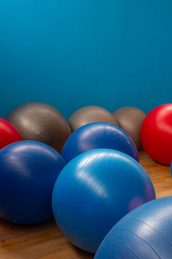 Colored balls Blue Indoors  Still Life Table Sport No People Red Close-up Multi Colored Fitness Ball Ball Sphere Colored Background Wellbeing Studio Shot Sports Equipment Focus On Foreground Copy Space Group Of Objects Blue Background