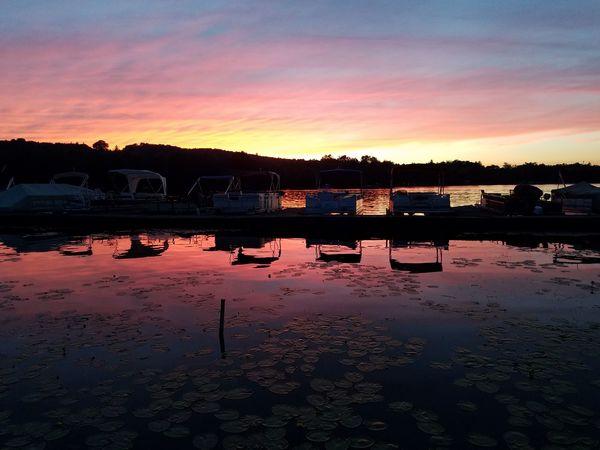 Sunset with pontoon boats docked Pontoonboats Docks Dockside View Sunset Orange Color Red Color Sky Dusk