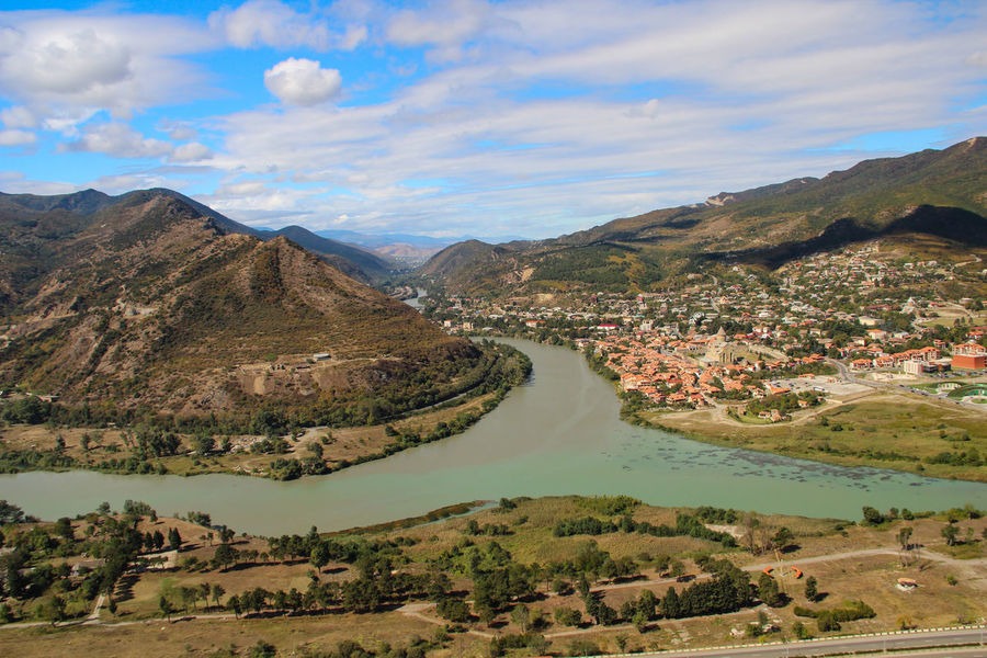 The merger of two rivers, Mtskheta, Georgia Beauty In Nature Day Geology Green Hill Landscape Mountain Mountain Range Outdoors Sky And Clouds Sky_collection Stream Tranquil Scene Valley Valley City Quiet Q Traveling In Georgia Landscapes With WhiteWall A Birds Eye View