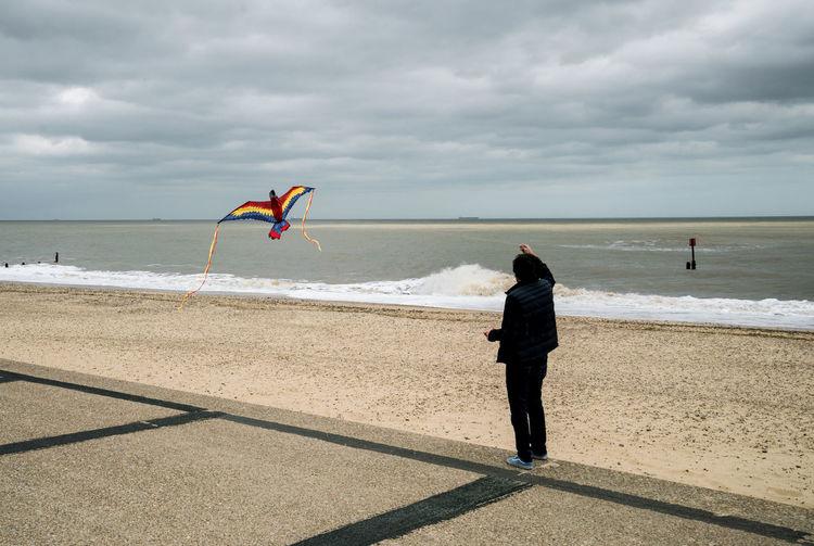 Full length of man flying kite by beach against sky