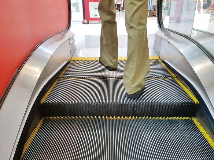 Low section of man on escalator