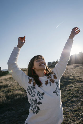 Happy woman with arms raised standing against sky