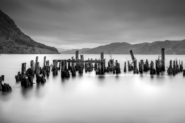 Panoramic view of wooden posts in sea against sky