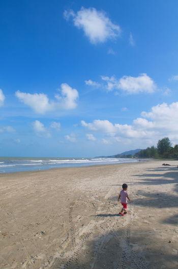 Boy walking on beach against blue sky