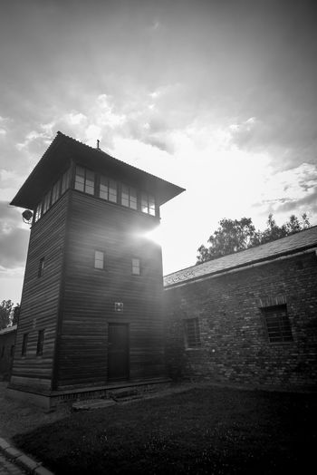 Auschwitz Auschwitz  Architecture Built Structure Building Exterior Sky Building Nature Cloud - Sky Low Angle View No People Day Plant Sunlight Tree Outdoors History The Past City Wall - Building Feature House Travel Destinations