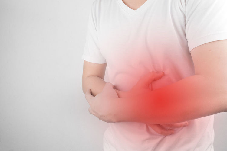 Midsection of man with stomachache standing against white background