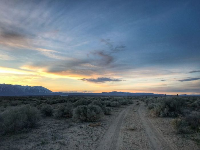 Dirt road amidst landscape against sky during sunset