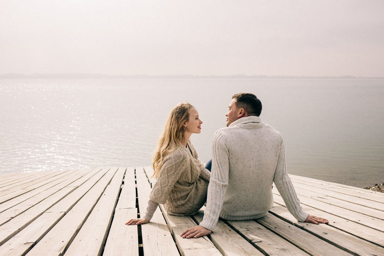 Rear view of couple sitting on pier by sea against sky