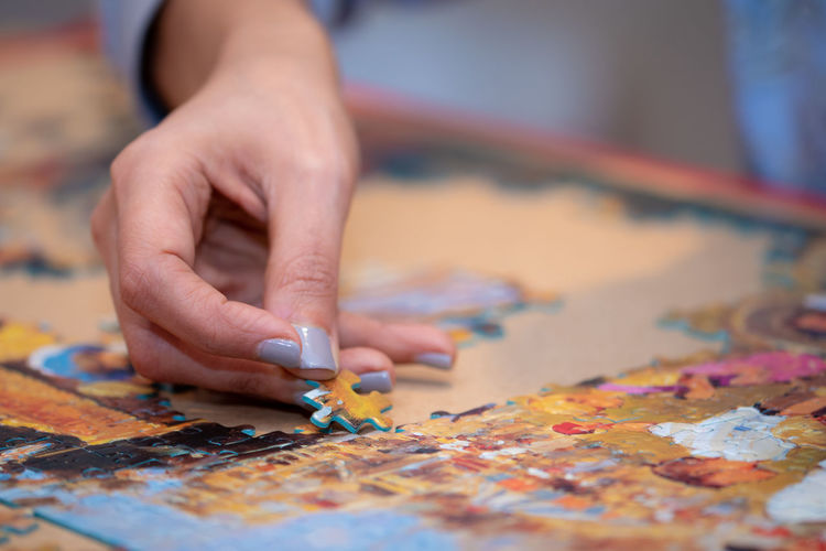 Close-up of woman hand arranging jigsaw pieces on table