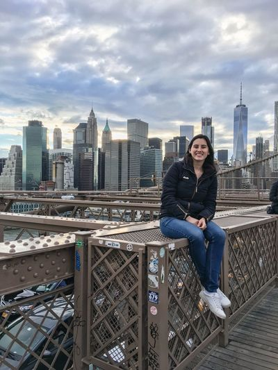 Portrait Of Smiling Young Woman Sitting On Brooklyn Bridge