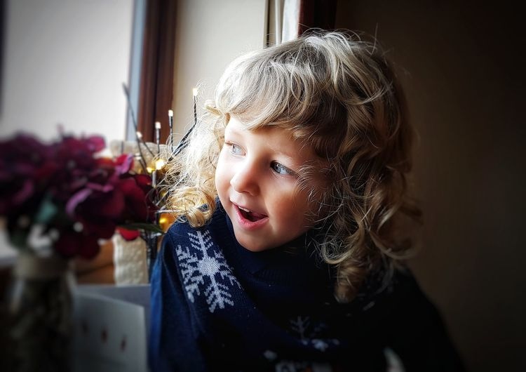 Close-up of girl looking through window at home