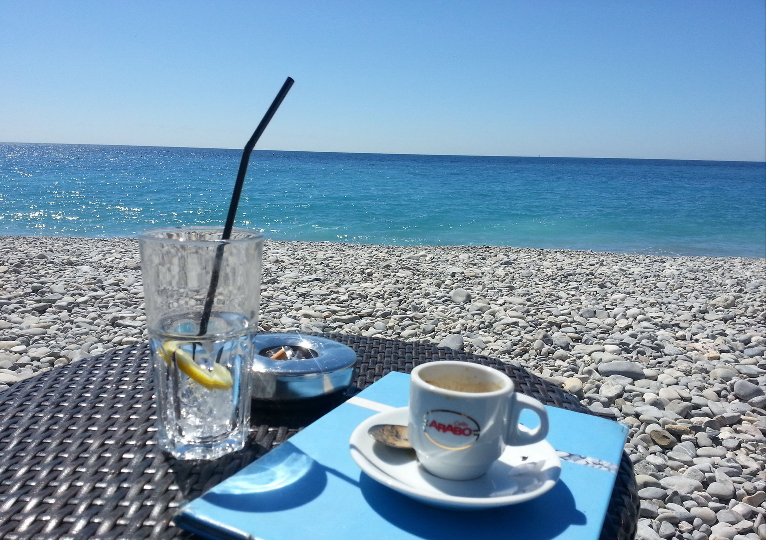 sea, horizon over water, water, blue, clear sky, beach, shore, tranquility, tranquil scene, copy space, table, sky, nature, food and drink, scenics, nautical vessel, day, drink, beauty in nature, sunlight