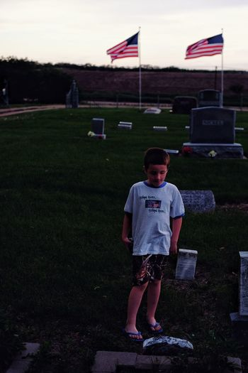 Boy standing by tombstone at cemetery