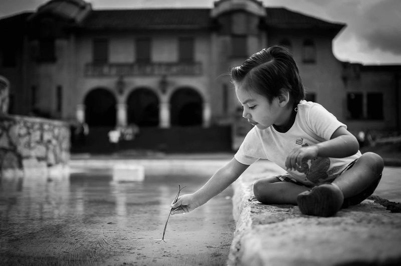 Boy Playing Against Building
