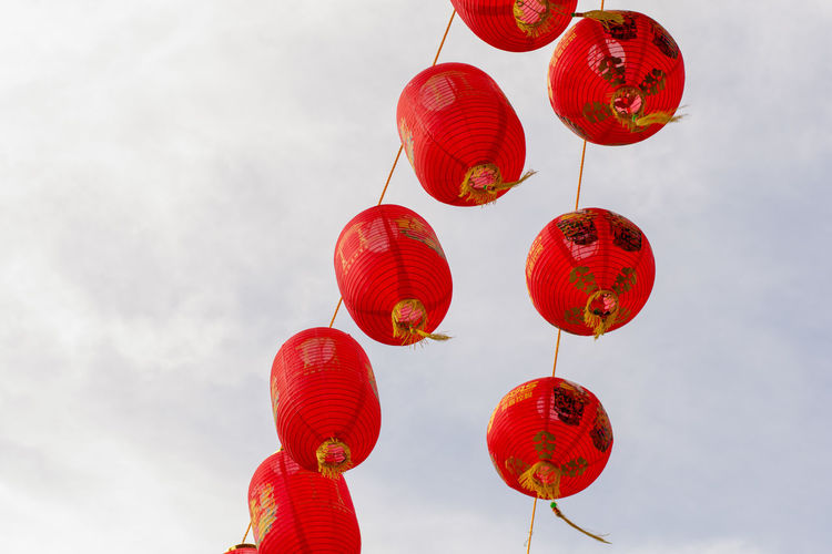 Low angle view of red lanterns hanging against sky