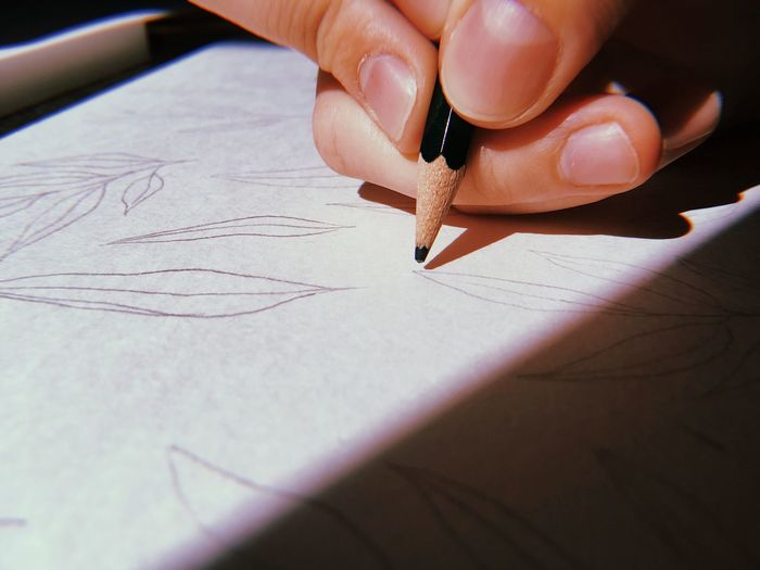 Cropped hand of person drawing on paper with pencil