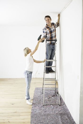 Blond haired lady passing a man on a ladder a drill Blond Hair Casual Clothing Day DIY Drill Full Length Ladder Leisure Activity Lifestyles Outdoors Passing Teamwork White White Walls