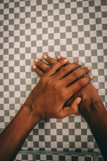 Cropped hands of man touching checked pattern tablecloth