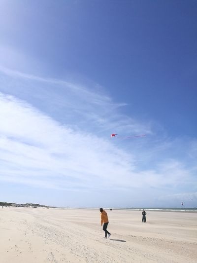 Full length of man flying kite at beach against blue sky