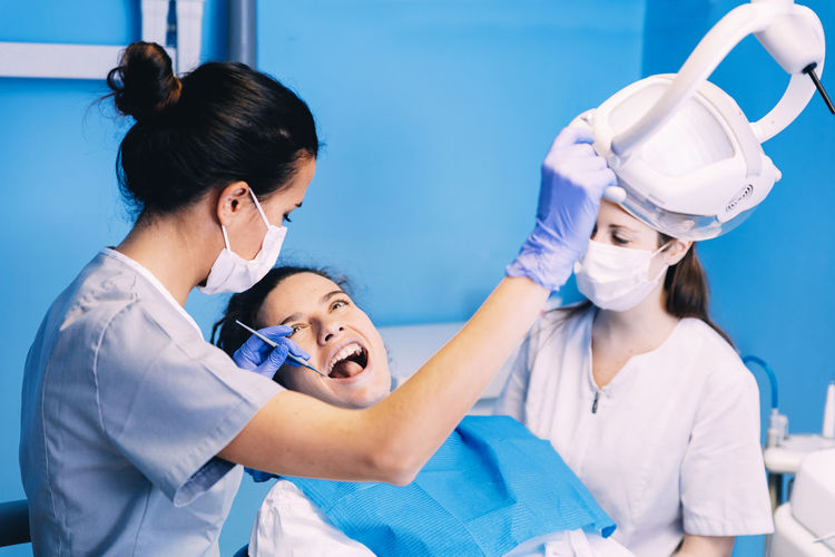 Dentists examining woman in clinic