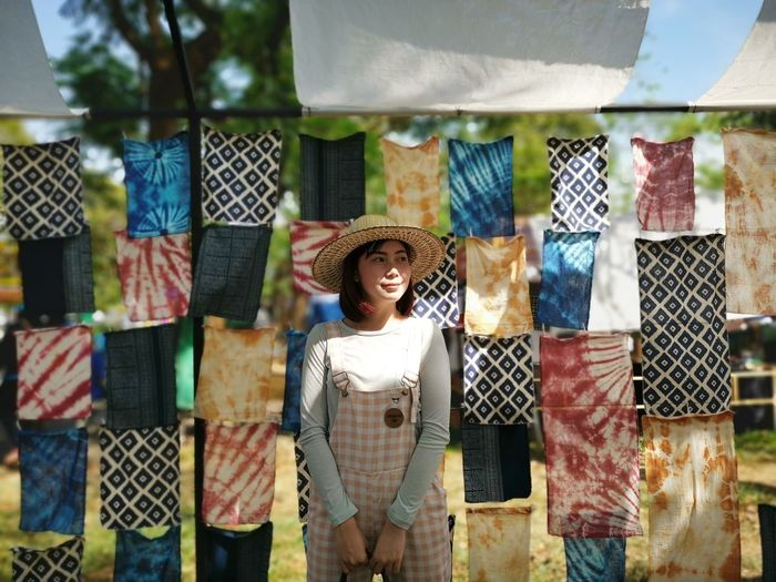 Woman standing against fabrics