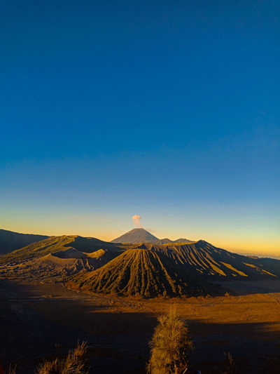 Scenic view of illuminated mountain against blue sky