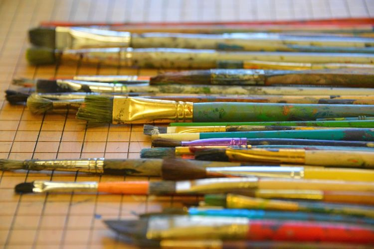 Close-up of multi colored paintbrushes on table