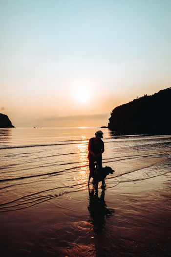 Silhouette senior woman with dog standing at beach against sky during sunset